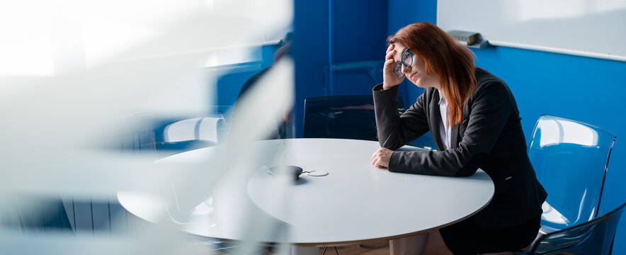 Tired red-haired business woman in glasses and a suit alone in an empty conference room. An office worker with a headache is waiting for the presentation to begin in the boardroom.