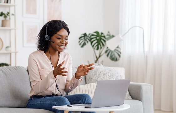 Video Conference. Smiling african woman having web call on laptop at home