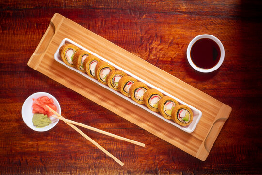 Wooden Table Served with Asian Food Consisting of Sushi with Crab and Avocado Stuffing, Banana Tempura around Rice Accompanied by Soya Sauce, Pickled Ginger, Wasabi and Sticks