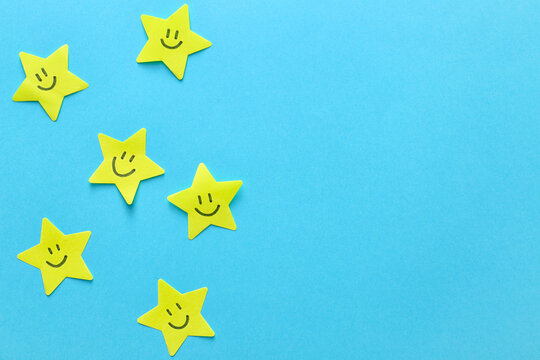 Paper stars with drawn happy faces on color background