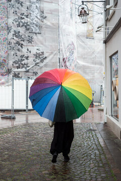 Portrait on back view of woman walking in the street with a rainbow umbrella
