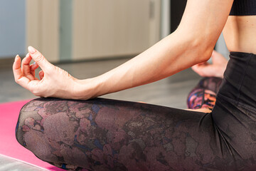 Woman meditating at home in the lotus position closeup. Relaxation and meditation