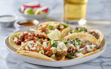 Wall Mural - platter of mexican street tacos with carne asada, chorizo, and al pastor in corn tortillas