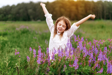 Wall Murals A little girl in a white dress with beautiful flowers in the field in summer. Concept of happy childhood. Copy space for text