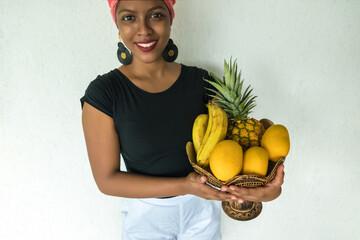 Happy Ethiopian girl carrying a fruit basket