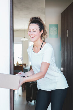 Beautiful caucasian young woman smiling receiving mail delivery package at home during covid 19 pandemic.