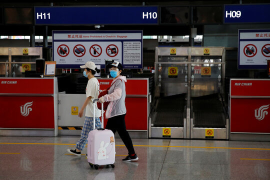 Women walk past check-in counters at Beijing Capital International Airport