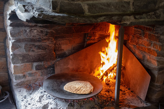 "Baking traditional Norwegian roundel (""lefse""). It is made on a hot metal plate in an open fireplace, the old way."