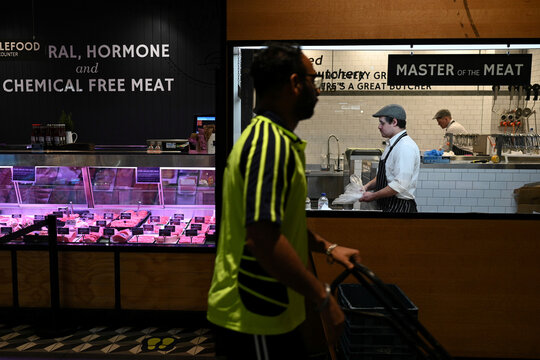 Butchers prepare meat for sale in a butcher shop in Sydney