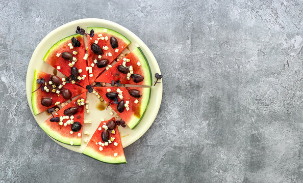 Savory watermelon pizza with feta, microgreens, kalamata olives, and balsamic. Top view, copy space