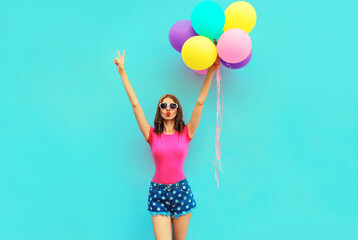 Beautiful young woman raising her hands up with bunch of balloons having fun wearing a shorts and...