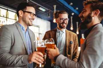 Business people drink beer after work in pub. Businessmen enjoy a beer.