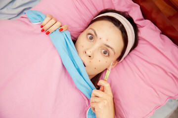 Portrait young woman with chickenpox lying in bed and measuring temperature