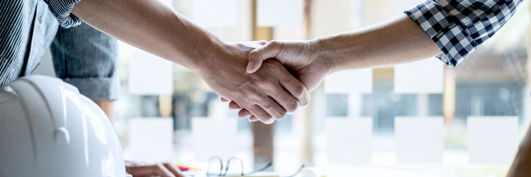 Two engineer shaking hands after consultation and conference new project plan