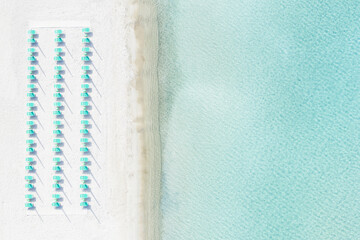 View from above, stunning aerial view of a white sand beach with beach umbrellas and a beautiful turquoise sea. Marinella Beach, Porto Rotondo, Costa Smeralda, Sardinia, Italy.