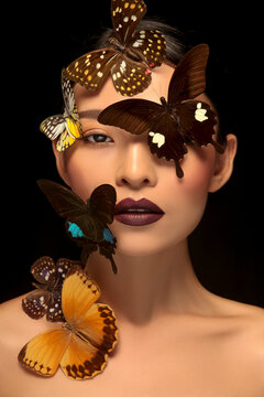 Asian woman decorating makeup face with butterfly taking makeup photo in black background