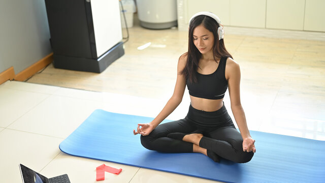 Young woman meditating and listening to music while sitting on an exercise mat.