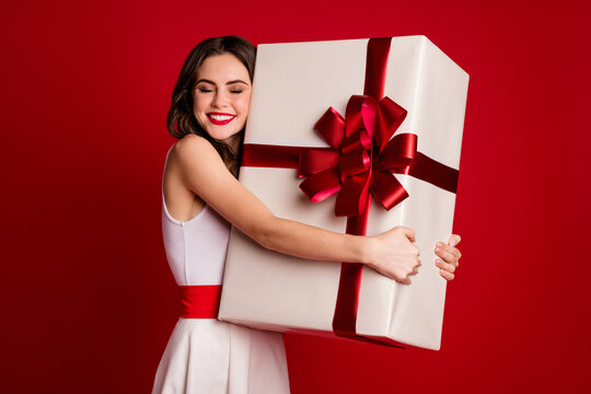 Portrait of her she nice attractive lovely cheerful cheery wavy-haired girl carrying hugging big white giftbox isolated on bright vivid shine vibrant red burgundy marsala maroon color background