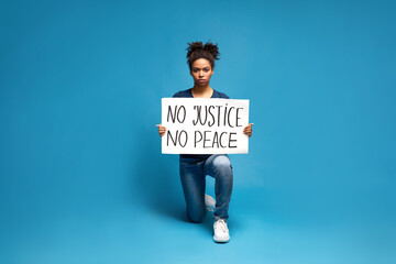Black woman protesting with poster No Justice No Peace