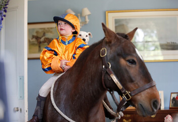 Merlin Coles 3, watches the horse racing from Royal Ascot on TV at his home