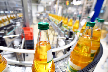 apple juice in glass bottles in a factory for the food industry - bottling and transport