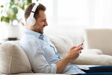 Happy man listening to music sitting on sofa