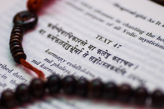 A text from Hindu sacred book Bhagavad Gita along with rosary.