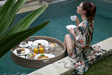 Woman enjoying floating breakfast, beautiful beginning of summer day