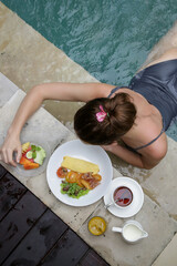 Top view of a young woman having a breakfast at the edge of the pool. Relaxed beginning of a summer day.