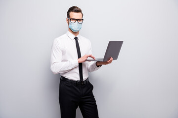 Portrait of his he nice skilled guy employer using laptop wearing safety gauze mask searching infro market research mer cov contamination prevention isolated grey color background