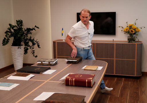 Ukrainian opposition politician Medvedchuk shows books from his collection during an interview in Kyiv