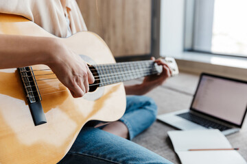 Image of young woman using laptop while playing acoustic guitar at home