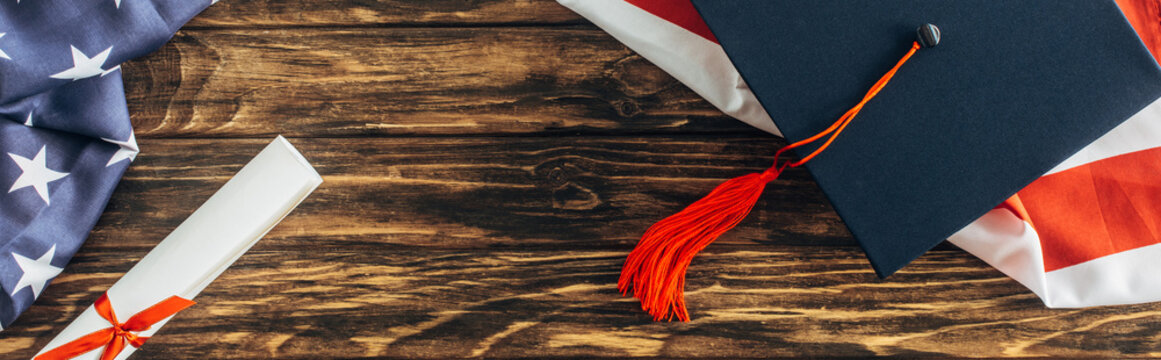 horizontal crop of graduation cap and diploma near american flag with stars and stripes on wooden surface