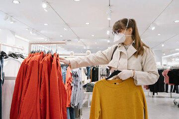 Woman with face mask and disposable gloves shopping in a fashion store