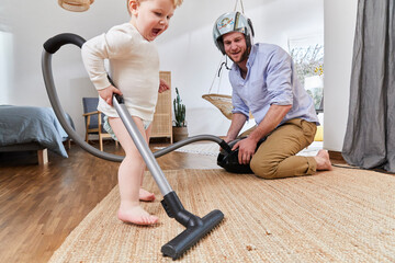 Cute baby boy cleaning carpet with vacuum cleaner by father in living room at home