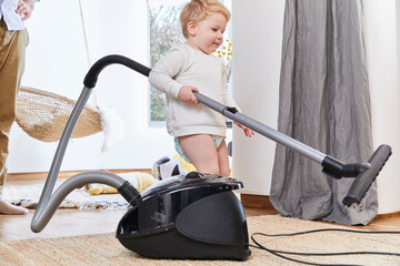 Cute toddler holding vacuum cleaner while standing on carpet by father at home