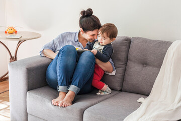 Happy mother sitting on couch cuddling her little son
