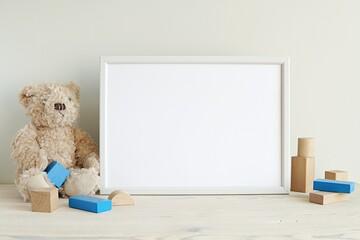 Horizontal white frame mockup for nursery art, photo or print, teddy bear and blue wooden building blocks.
