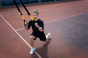 yound sporty athlete or bodybuilder has fitness workout with trx outdoor
