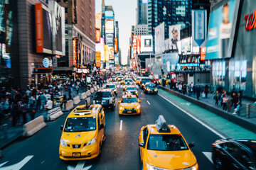 Motion blur effect,Times square with illuminated buildings and advertise on front crowded streets and yellow cabs for transportation tourists,midtown in New York with busy traffic and taxi cars moving