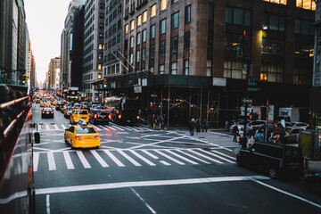 Traffic on avenue roads in midtown with yellow taxi and cars rushing in jam, Manhattan buildings on avenue in New York with a lot of transport driving in evening time, Environmental impact reduction