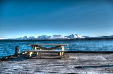beautiful wooden bench on old wooden pier with blue fjord and white snowy mountain background