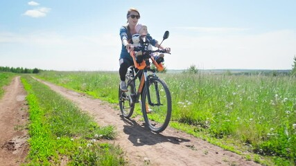 Wall Mural - Family cycling. Woman riding bicycle with baby on the front seat on a rural road and summer green meadow