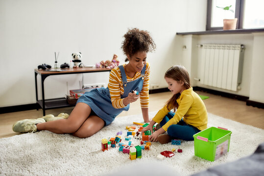 We like to play. Caucasian little girl spending time with african american baby sitter. They are playing with construction toys set, sitting on the floor