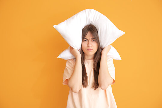 Tired woman with pillow on color background. Concept of sleep deprivation