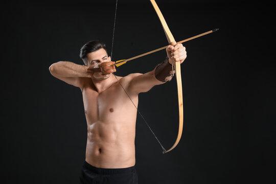 Handsome man with crossbow on dark background