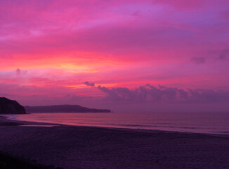 Pink Sunrise in Japan at the beach. Dawn early summer sky before a storm. Pacific ocean sky with headland