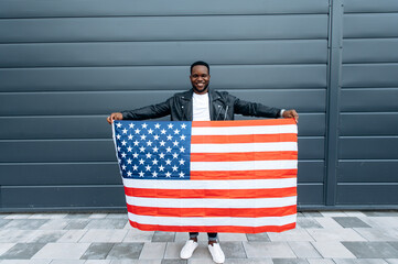 Attractive happy stylishly dressed african american guy stands outdoors and holds the usa flag in...