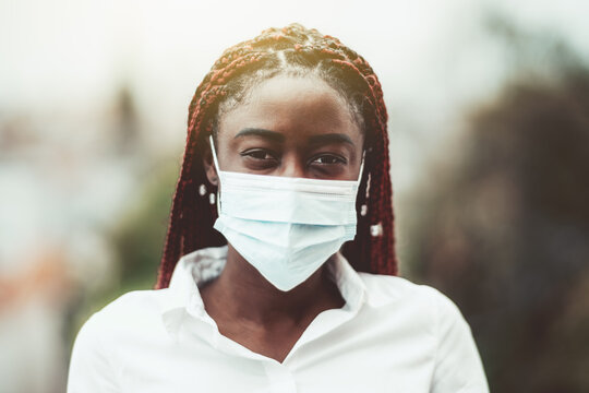 An outdoor portrait of a young African female with chestnut braids and in a virus protective mask on her face; masked black woman outdoors with protection against influenza and pandemic threat