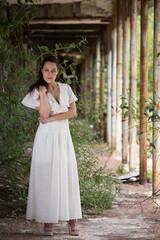 Beautiful young woman wears a long white dress